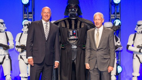 Disney Consumer Products President, Bob Chapek, left, and Lucasfilm Executive Vice President Howard Roffman pose with Darth Vader and 20 Stormtroopers as they take over the stage during a private Disney event at the Licensing Expo, Monday June 17, 2013 at the Mandalay Bay Convention Center in Las Vegas. This surprise grand finale, presented to  more than 1,500 licensees, demonstrates a new era of merchandising potential for Disney Consumer Products¹ robust franchise portfolio, which now includes the Star Wars franchise. (Photo by Eric Jamison/Invision for DisneyConsumer Products/AP Images)