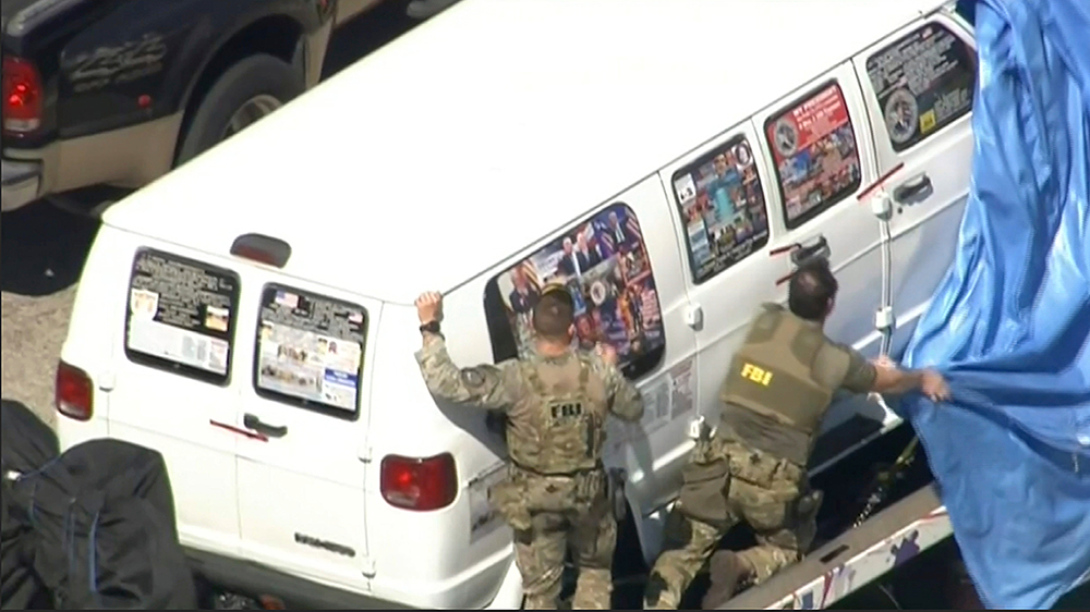 This frame grab from video provided by WPLG-TV shows FBI agents covering a van after the tarp fell off as it was transported from Plantation, Fla., on Friday, Oct. 26, 2018, that federal agents and police officers have been examining in connection with package bombs that were sent to high-profile critics of President Donald Trump. The van has several stickers on the windows, including American flags, decals with logos and text. (WPLG-TV via AP)Explosive Devices, Plantation, USA - 26 Oct 2018