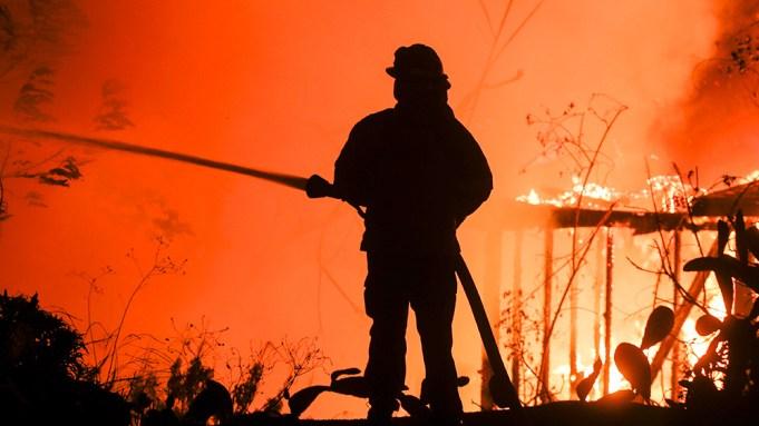 A firefighter battles the Woolsey Fire