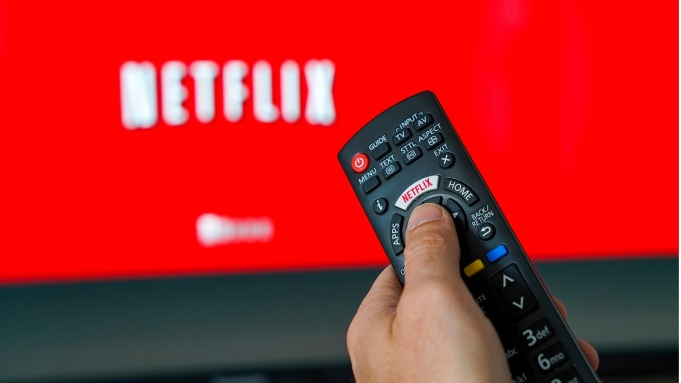 Illustration of the video streaming company Netflix. Logo Netflix on the keyboard of a remote control in front of a TV.Netflix, Belgium - 01 Apr 2019