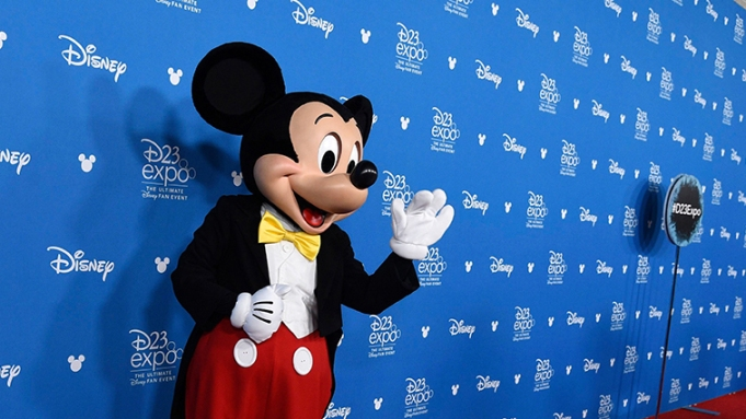 Mickey Mouse waves to members of