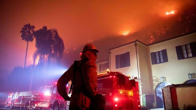 A firefighter watches a flames approach