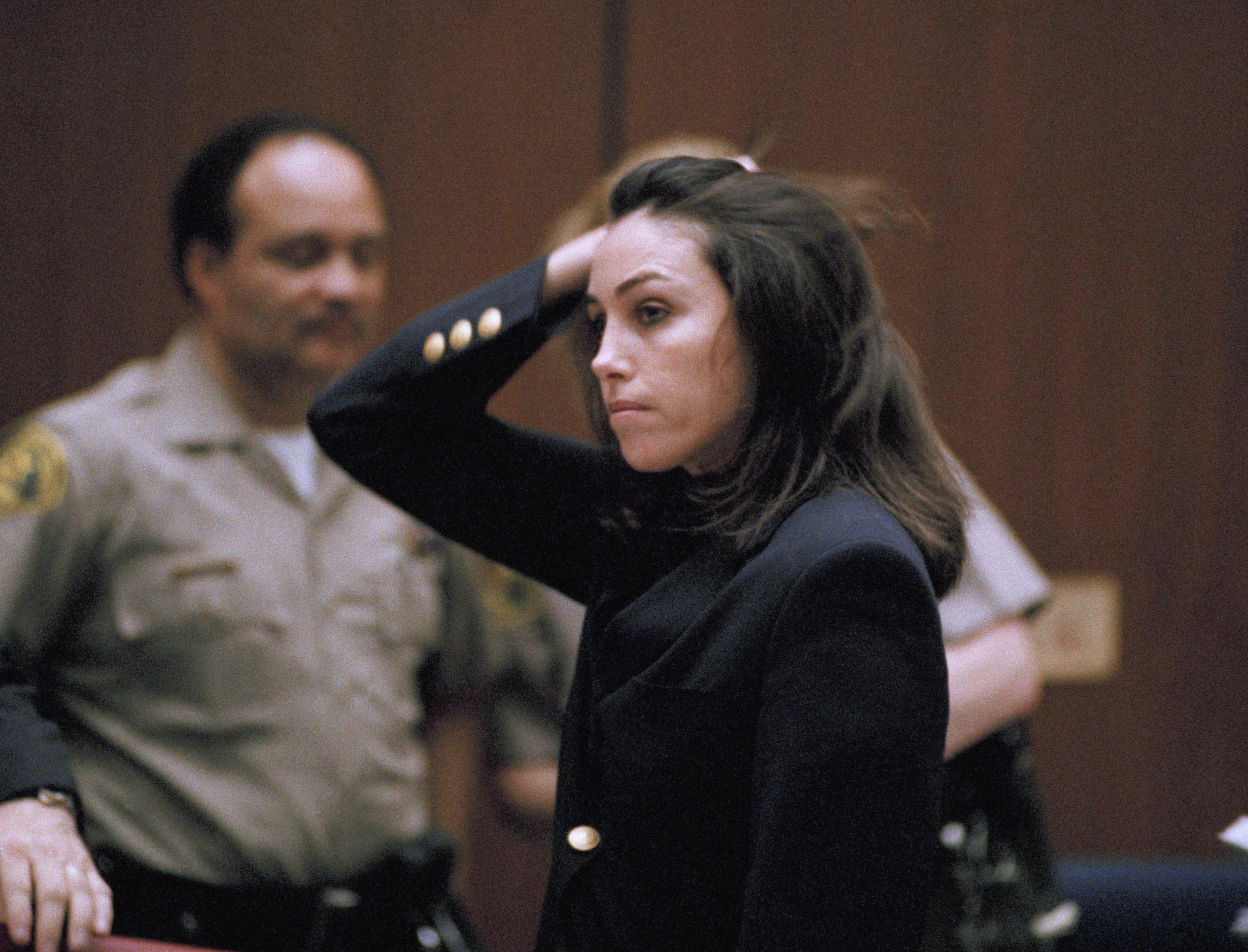 "Reputed ""Hollywood Madam,"" Heidi Fleiss brushes back her hair as she listens to her attorneys ask Superior Court Judge Judith Champagne to determine if jurors in her case violated their deliberations by improperly discussing the case outside the jury room, Jan. 30, 1995, in Los Angeles. Fleiss remains free on bail. (AP Photo/Chris Martinez)"