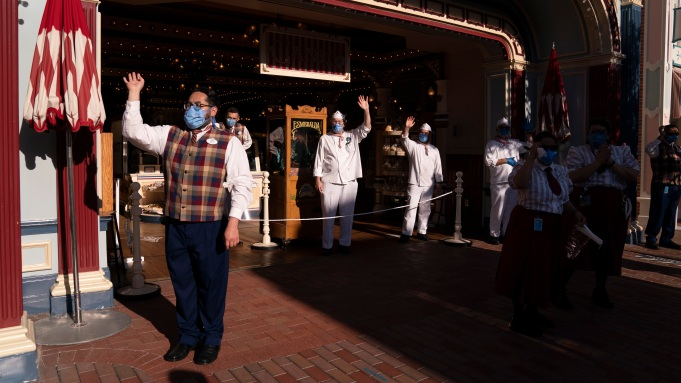 Employees wave as guests walk along