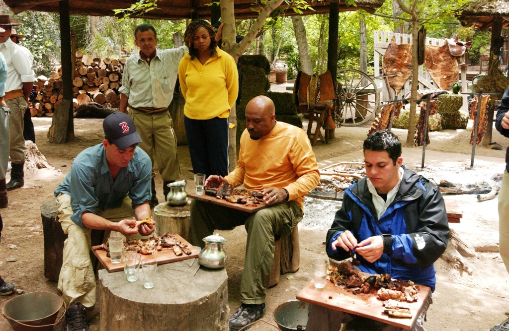 """caption: """"Do You Need Some Mouth-To-Mouth Resuscitation?"""" --Joyce looks on as Rob, Uchenna and Alex perform the Roadblock Challenge in Mendoza, Argentina, requiring one team member to consume 4 lbs of a traditional Argentinean barbeque on THE AMAZING RACE 7, broadcast Tuesdays on the CBS Television Network. Photo: Tony Esparza/CBS ©2005 CBS Broadcasting Inc. All Rights Reserved copyright:"""