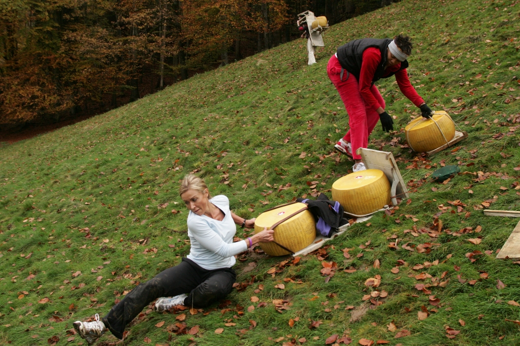 """""""Don't Let a Cheese Hit Me""""--Jodi (left) and Jen travel with their teams to Interlaken, Switzerland and perform a """"cheese race"""" in which they carry wheels of cheese up and down a slope to a little alpine hut in order to receive their next clue, on THE AMAZING RACE 14, Sunday, Feb. 15 (8:00-9:00 PM, ET/PT) on the CBS Television Network. Photo: Robert Voets/CBS ©2008 CBS Broadcasting Inc. All Rights Reserved."""