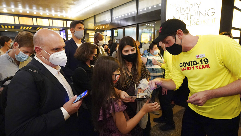 """Theatergoers show proof of vaccination before a performance of """"The Lion King"""" on Broadway, at the Minskoff Theatre, on Tuesday, Sept. 14, 2021, in New York. (Photo by Charles Sykes/Invision/AP)"""
